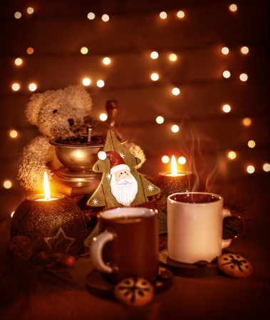 Closeup on beautiful Christmastime still life, coffee cups with tasty cookies, teddy bear and decorative wooden tree on glowing background photo