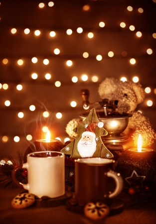 Festive still life on the table, beautiful glowing garland on the wall, two mugs with tea with homemade gingerbread, burning candle, Christmas decoration photo