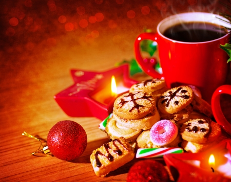 Christmas sweets still life on wooden table in cozy cafe, red cup with coffee, homemade gingerbread, warm candle light, traditional Christmastime sweets  photo