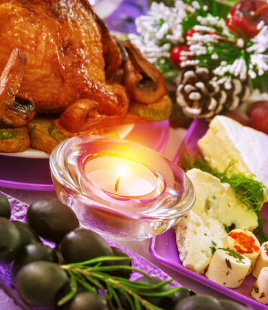 Christmastime banquet, festive table setting with bright candle light, New Year eve, tasty baked chicken, black olives, pine cone with snow decoration photo