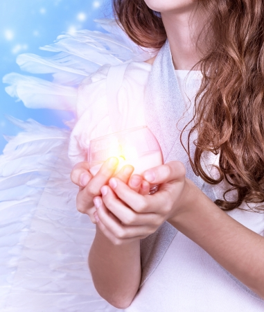 Closeup on little angel holding in hands candle, body part of teen girl wearing white dress and big fluffy wings holiday concept photo