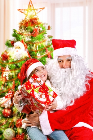 Little happy girl receive gift from Santa Claus, sitting near beautiful decorated Christmas tree, enjoying Xmas eve at home Stock Photo - 24424826