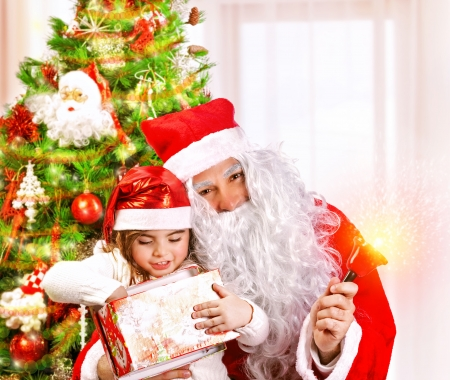 Christmas party for children at home, adorable little girl and old Santa Claus with big white beard open Christmas present, happiness concept photo
