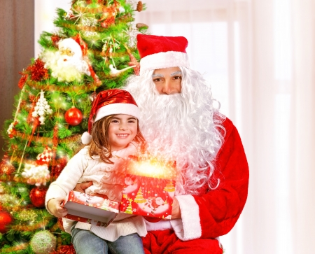 Santa Claus with granddaughter sitting near Christmas tree, cute girl opening gift box, glowing lights, magic night, fairy tale concept photo
