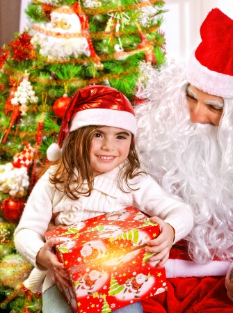 Little happy girl receive gift from Santa Claus, sitting near beautiful decorated Christmas tree, enjoying Xmas eve at home Stock Photo - 24424872