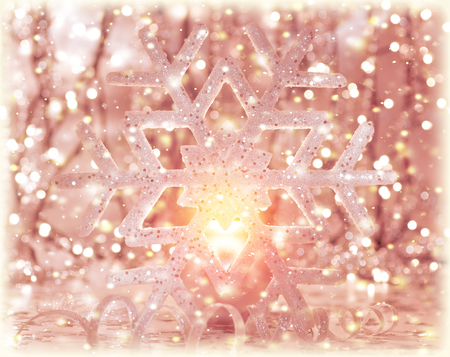Beautiful pink Christmas time decoration, shiny snowflake with bright candle light and ribbon decor photo
