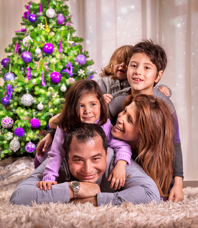 Portrait of happy arabic family lying down near beautiful decorated Christmas tree, celebrating holiday at home, happiness concept photo