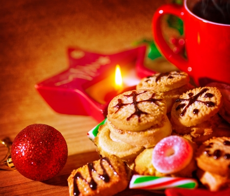 Closeup on tasty sweet homemade gingerbread with cup of tea, star shape candle, festive christmas decoration, traditional Christmastime dessert  photo