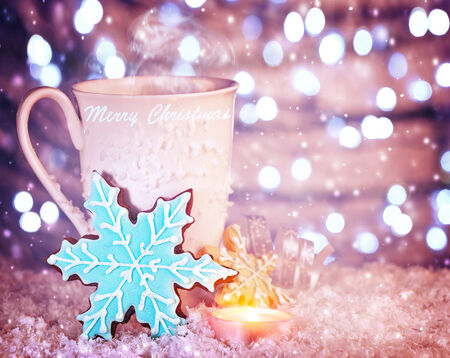 White cup of coffee with blue snowflake shaped gingerbread, warm cozy candle light, beautiful still life of Christmas dessert photo