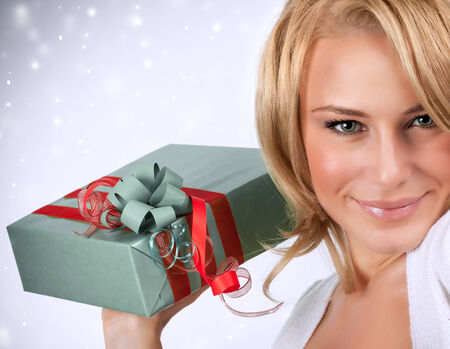 Closeup portrait of sexy woman holding in hands gray gift box with red ribbon, Christmas surprise, getting present concept photo