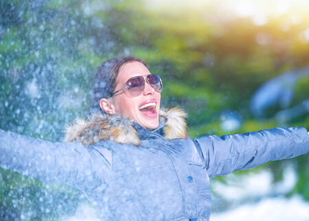 active lifestyle: Playful woman having fun on winter park, throwing snow, enjoying wintertime nature, active lifestyle, happiness concept