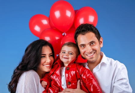 happy family concept: Closeup portrait of young parents carry sweet adorable son outdoors, beautiful red balloons, active lifestyle, happy family concept