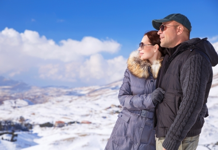 family activities: Happy couple in snowing mountains, active lifestyle, winter vacation, luxury wintertime resort, loving family, cold weather