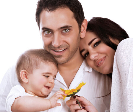 Young family portrait in the studio on white background, touching beautiful fresh yellow sunflower, adorable joyful baby, togetherness concept photo