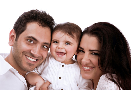 Cheerful young family portrait in the studio, happy parents with sweet little baby girl isolated on white background, love concept photo