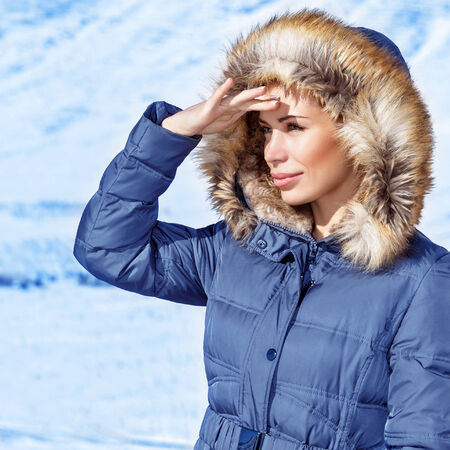 Woman looking away, wearing warm stylish blue coat with furry hood, wintertime fashion, cold weather, winter holidays concept photo