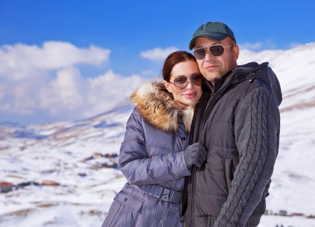 cold weather: Portrait of happy couple spending winter vacation in the mountains, ski resort, cold weather, romantic relationship concept