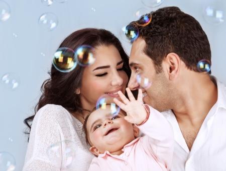 burbujas de jabon: Primer retrato de la joven familia feliz jugando con pompas de jabón sobre fondo azul, se divierten, juegan al juego, la felicidad y la alegría concepto