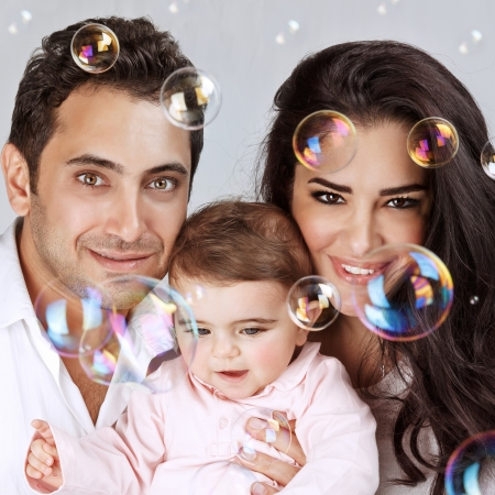 Closeup portrait of cute little baby girl with lovely parents enjoying soap bubbles, playing with bubbles water, happy childhood concept photo