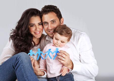 familia unida: Retrato de Linda familia árabe sentado en el estudio y la participación en las manos de papel pegado hombres-forma azul, la gente el concepto de unidad