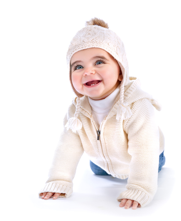 Closeup portrait of cute active baby crawling in the studio, wearing white stylish knited hat and hoody, wintertime fashion for children photo