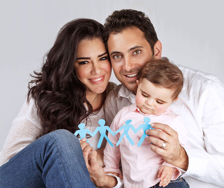arab men: Portrait of cute arabic family sitting in the studio and holding in hands blue men-shape bonding paper, connection of people concept Stock Photo