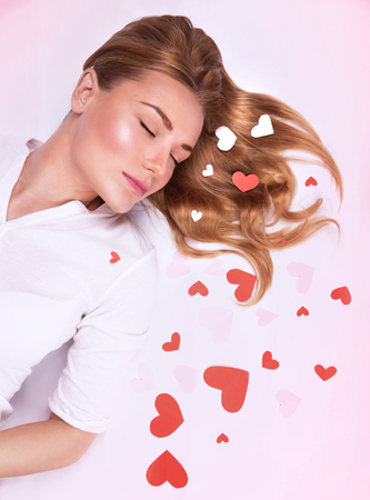 Romantic fashion model lying down on the floor with closed eyes decorated with many little red hearts, dreaming about love, Valentine day concept   photo