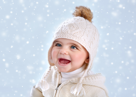 Portrait of cute little baby girl wearing warm stylish hat isolated on blue snowy background, snow falling, winter season, happy child concept photo