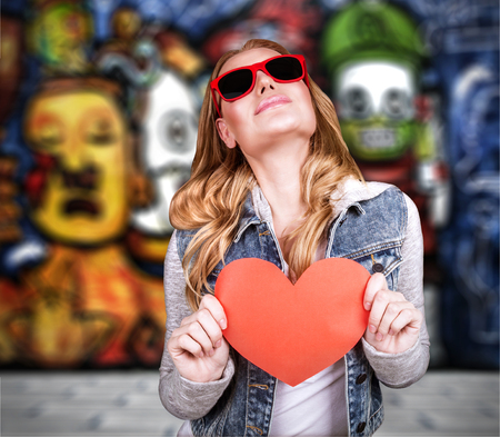 Graffiti urban lifestyle, funky culture, stylish teen girl wearing sunglasses and holding red paper heart, modern love concept photo