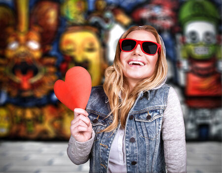 Funky teen girl in love, having fun outdoors, holding in hands  red heart as symbol of adolescents affection, urban lifestyle, stylish colorful graffiti on the wall behind young lady photo