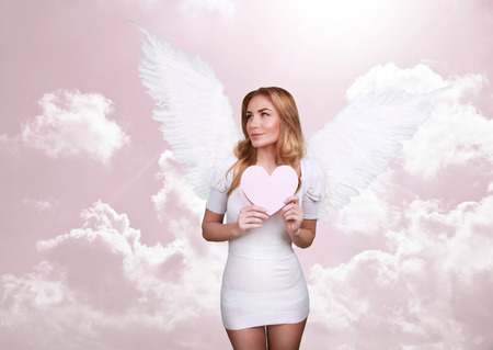 heart with wings: Angel of love, beautiful girl with great white feather wings in the heaven, pink cloudy sky, Valentine day, romantic holiday concept