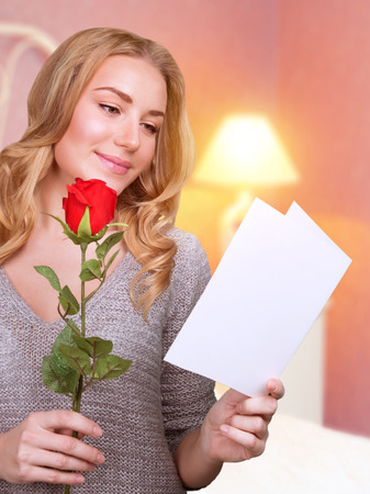 Portrait of cute blonde girl reading love letter with red rose in hand at home, receive festive postcard from lovers in Valentines day photo