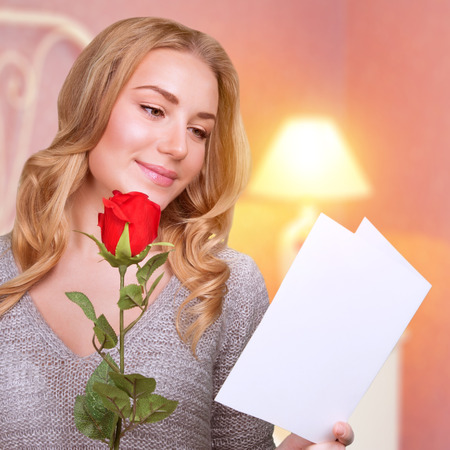 Romantic woman in Valentine day receive greeting card, enjoying fresh red rose, cozy home interior, getting gift with love, romance and affection concept photo