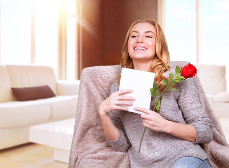 pleasure of reading: Happy female enjoying greeting card, reading with pleasure love letter, receive red rose, celebrate Valentine day at home
