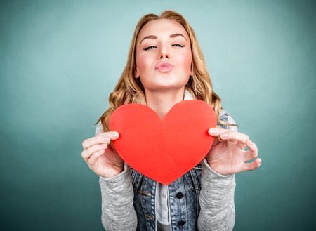 love kissing: Portrait of cute teen girl with red paper heart isolated on gray background, kiss with love, Valentine day, affection concept