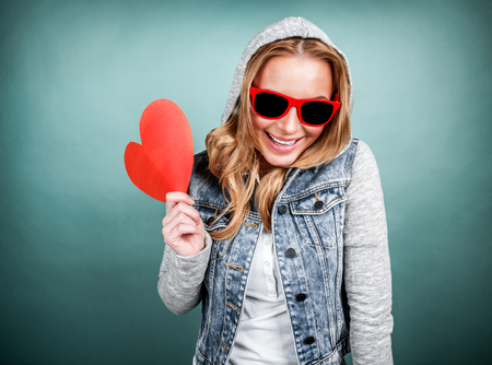 Happy romantic girl laughing on blue background, wearing stylish jacket with hood and sunglasses, holding red heart-shaped Valentine day card photo