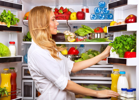 Happy female search something in the fridge, fresh fruits and vegetables in the refrigerator, cooking diet food, fit and body care concept