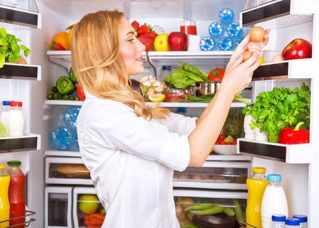 健康、新鮮なおいしいオーガニック食品、健康的な食事の概念についてかわいい女性を魅力的な主婦、冷蔵庫から卵の世話します。