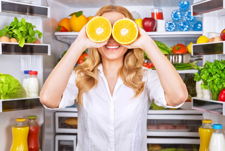 two and a half: Joyful female on the kitchen playing with two half of orange, tasty juicy fruit instead eyes, healthy nutrition, fun and joy concept Stock Photo