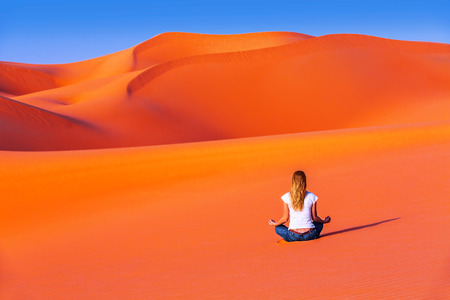 Meditation in desert, healthy active lifestyle, young female sitting alone on hot orange sand, zen balance, beautiful nature, peace and relaxation concept photo
