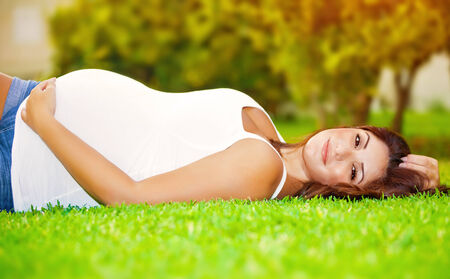 Cute pregnant woman lying down on fresh green grass on the backyard, happy parenthood, healthy pregnancy, spring season photo