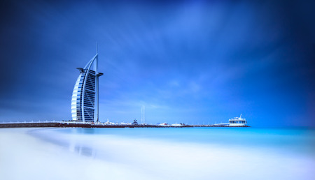 arab: Burj Al Arab hotel on Jumeirah beach in Dubai, modern arabic architecture, luxury beach resort, summer vacation and tourism concept