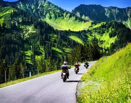 Group of travelling bikers in Alpine mountains, riding on mountainous highway, extreme lifestyle, spring travel and adventure concept  Stock Photo