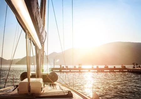 일몰에 요트, 고급스러운 물 수송, 바다에 밝은 태양 빛, 항해 요트 저녁 여행, 여름 휴가, 스포츠 개념을 요트 스톡 콘텐츠