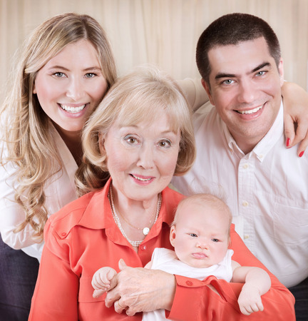 beautiful elegant grand mother holding on hands newborn granddaughter, mother and father standing behind them photo