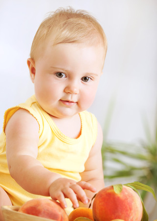 Happy little baby girl eating with fresh tasty fruit photo