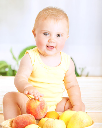 Happy little baby girl with fresh tasty fruits photo