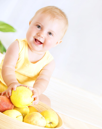 Happy little baby girl eating fresh tasty fruits for lunch, enjoying healthy food at home, organic nutrition for kids photo