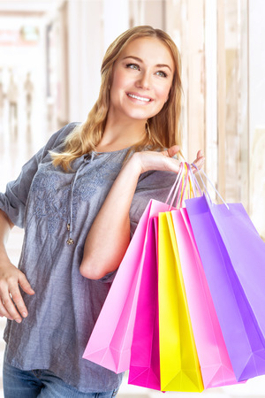 Portrait of sweet cheerful girl standing in big shopping centre with colourful paper bags, doing purchase with pleasure photo