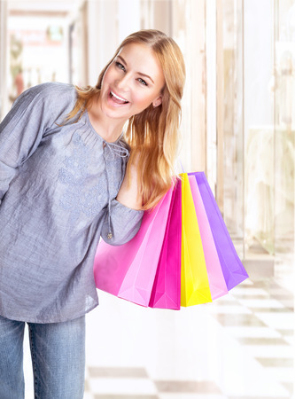 Excited woman with shopping bags in the mall, buying presents, happy consumer, spending money in fashionable boutique photo